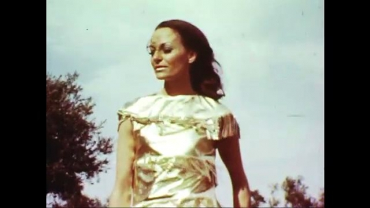 UNITED STATES: 1960s: lady models outfit on grass. Horses ride past model. Belt on outfit.  Vintage car