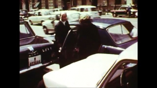UNITED STATES: 1960s: lady gets into car. Lady wearing sunglasses. Lady makes notes. Women cross road