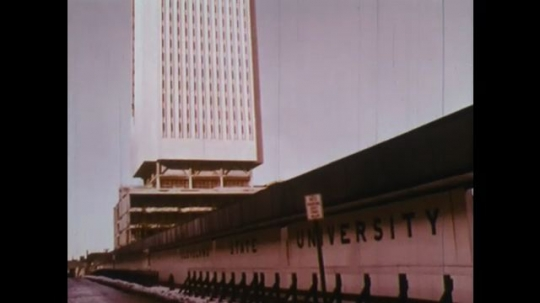 UNITED STATES: 1950s: Skyscraper against sky. People enjoy recreation. Workers on construction. Train on tracks
