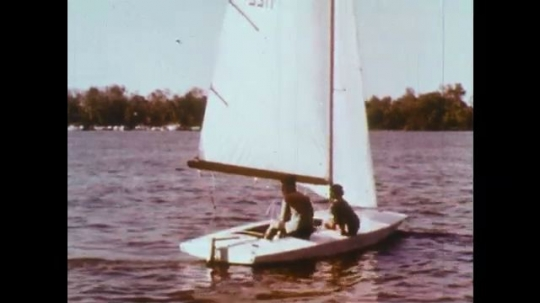 UNITED STATES: 1950s: man and boy on sailing boat. Speed boat on water. Boats in harbour