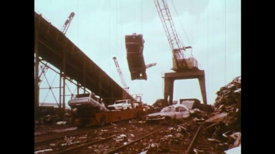 UNITED STATES: 1950s: crane lifts cars on to crusher. Scrap yard machines