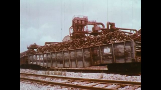 UNITED STATES: 1950s: train carries refuse. Man throws trash into rubbish truck.