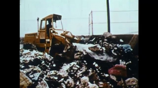 UNITED STATES: 1950s: digger moves rubbish in dump. Metal attached to magnet. Waste collection and processing plant