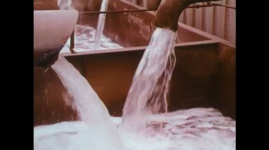UNITED STATES: 1950s: water from pipe enters container. Clay falls into tank. Hand opens drawer