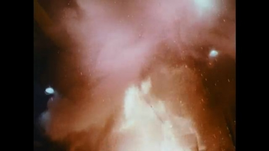 UNITED STATES: 1950s: blast furnace inside processing plant. Flames inside container. Machine pours liquid