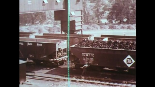 UNITED STATES: 1950s: raw materials on train cars in processing plant. View across industrial site