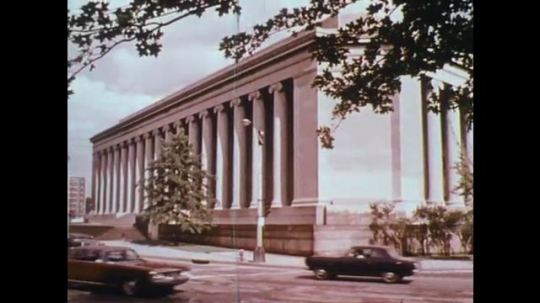 UNITED STATES: 1950s: cars drive past large building. Man fixes machine. Lady in lab.
