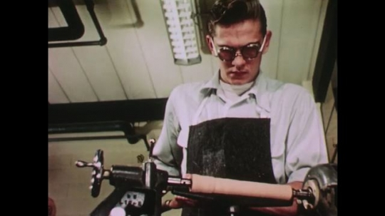 UNITED STATES: 1950s: boy chisels lines into wood carving