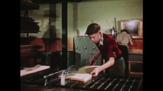 UNITED STATES: 1950s: boy cuts wood with circular saw. Boy moves wood. Boy adjusts blade.
