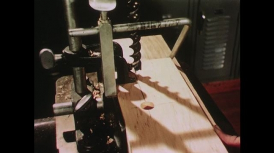 UNITED STATES: 1950s: hand sets up drill machine. Drill makes hole through wood. Boy blows away dust.