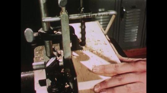 UNITED STATES: 1950s: student drills hole in wood. Boy uses jigsaw machine.