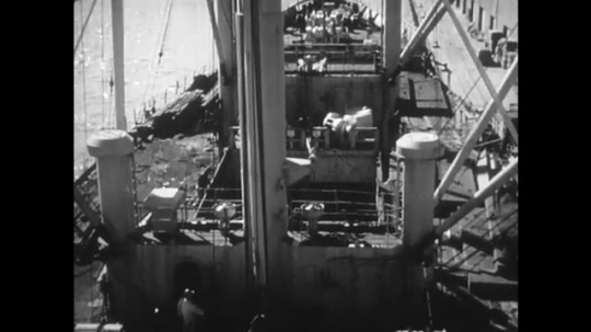 1950s: High angle view of ship, crane lifts bags. Officer talks into camera. Men on ship. Crane lifts cargo from ship.