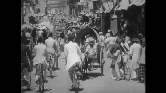1950s: People at street market. Tracking shot down city street. Men outside store window. Hands touch bolt of cloth. Hands give perfume to woman, woman smells bottle.
