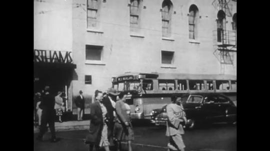 1950s: Pedestrians cross street. Officer on ship talks into camera. Man working crane, lifts bags of cargo.