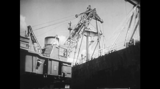 1950s: Crane on ship. View of mine. Men digging at mine. Man working in water. Women washing tin. Close up of woman working. Men move metal bars. Crane rotating.
