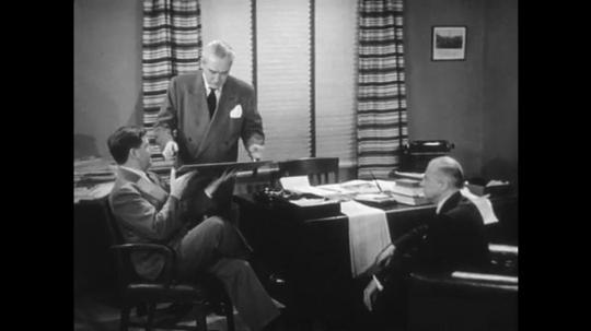 1950s: Men talking in office.