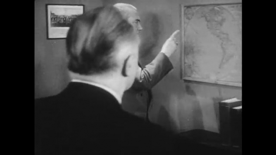 1950s: Men in office look at map.