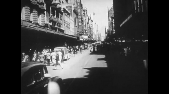 1950s: Tracking shot down city street. View of Oxford Street, Selfridges department store. Officer talks into camera. Ship at sea.
