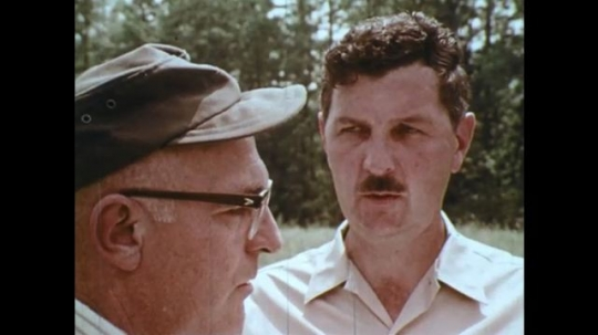 UNITED STATES: 1970s: men talk in field by woods. Man holds clipboard.