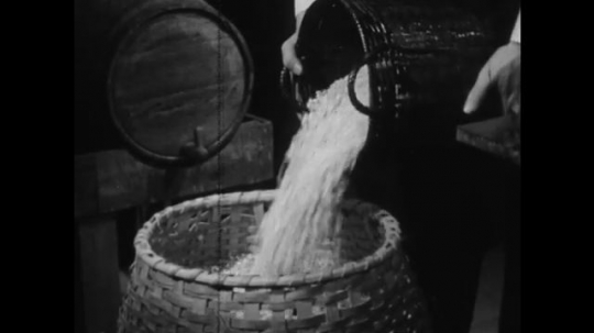 1950s: UNITED STATES: grain poured into basket. Barley poured into container. Man arrives at store. Man takes off hat