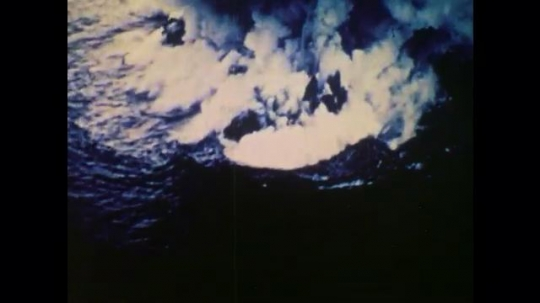 1970s: UNITED STATES: overhead view of volcanic eruption in ocean. Formation of an island