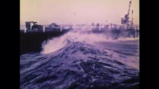 1970s: UNITED STATES: wave crashes into coastal protection. Wood smashed by waves travels towards coast. Clouds in sky from plane. Tsunami damage on land