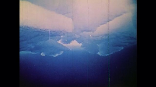 1970s: UNITED STATES: ocean ice seen from below. Man in submarine. Submarine surfaces under ice. Men sit on submarine roof in ice