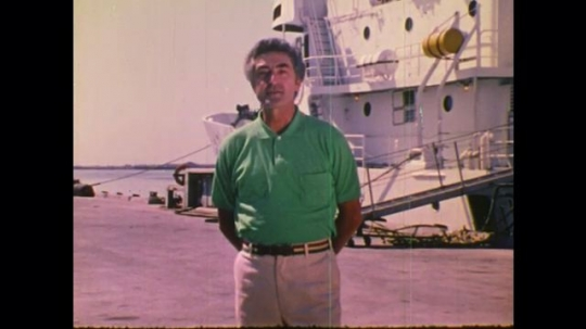 1970s: UNITED STATES: man by ship speaks to camera. Fish in water. Surface of sea bed. Ship at sea