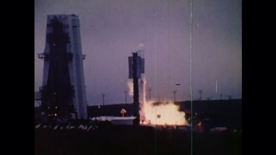 1970s: UNITED STATES: rocket takes off from launch pad. Rocks in sky. Satellite over Earth.
