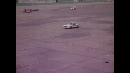 1970s: UNITED STATES: test car drives along track. Test car drives into vehicle