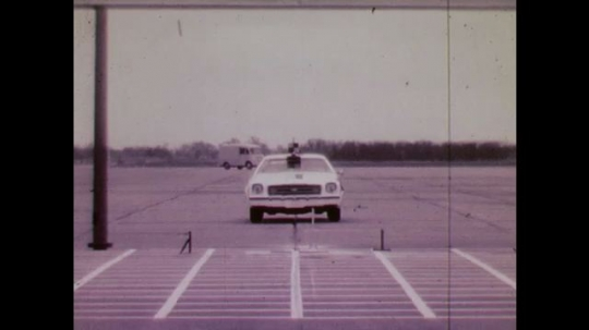 1970s: UNITED STATES: front view of test car on track. Slow motion of vehicle crash. Car hit on wing. Cars skid.