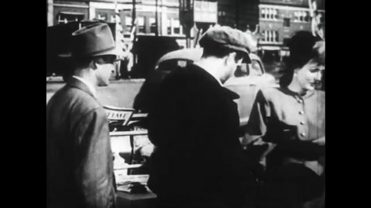 1950s: Man waits to buy paper. Man speaks to salesman. Man pays for newspaper. Man argues with salesman.
