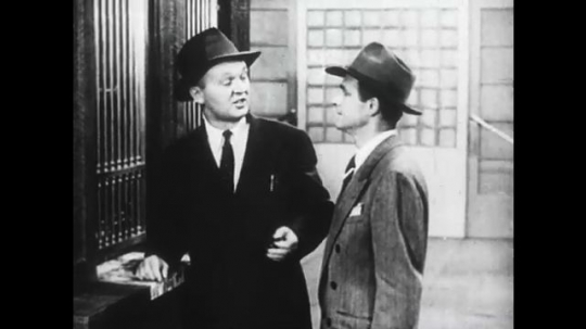 1950s: Man speaks to man in line. Man responds to man at ticket counter. Man turns and smiles. Man responds to man in line. Man walks to crowded elevator. Woman with packages enters elevator.