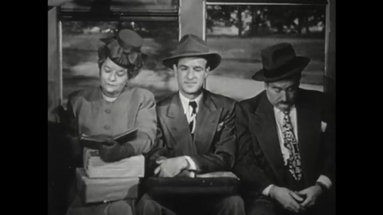 1950s: Man sits on crowded train. Man nods and smiles. Man walks into bank. Banker speaks to man. Man seats himself.