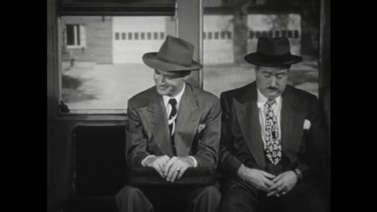 1950s: Man smiles and shakes head. Man speaks. Man slides away from passenger. Man speaks.