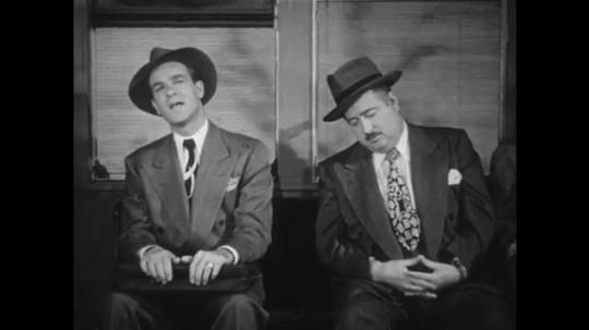 1950s: Man on train asks question. Man on balcony speaks.