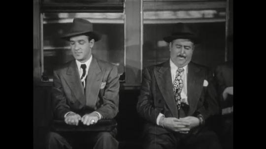 1950s: Man on train speaks. Man on train listens. Man and woman stand on balcony. Man on balcony speaks.
