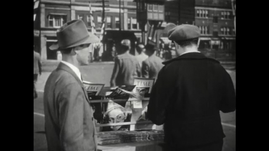 1950s: Salesman turns away. Man speaks to salesman and points across street. Salesman responds and hands man paper. Man speaks to salesman. Salesman talks to man.