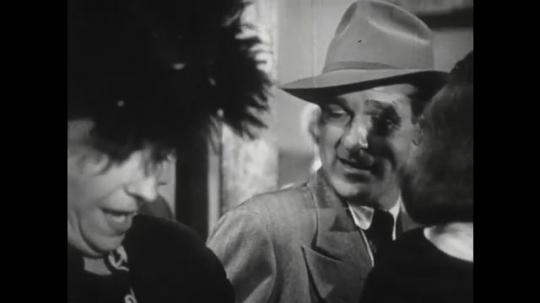 1950s: Man talks to woman. Man shifts in crowd. Man and woman talk.