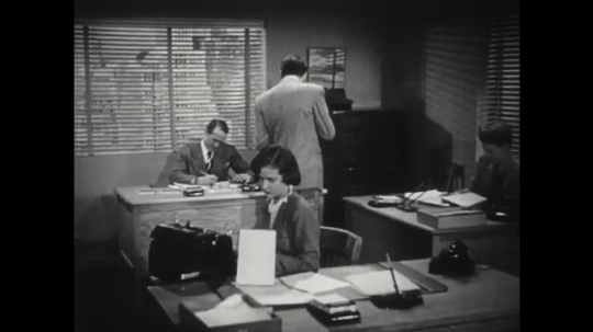 1950s: Co-worker paces around office and speaks. Co-worker points finger and talks. Co-worker leans on file cabinet.
