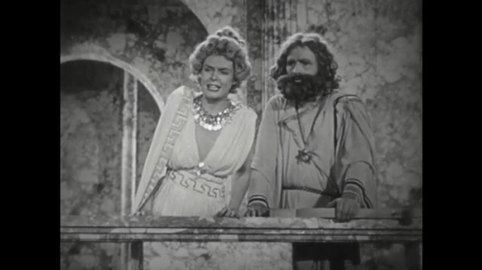 1950s: Man and woman stand on balcony. Woman speaks to man. Man responds to woman. Man and woman peer over edge of balcony.
