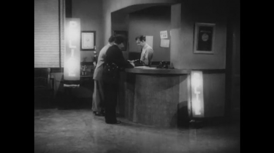 1950s: Policeman in uniform stands at precinct desk. Arrested person and receptionist talk with policeman at desk. Policeman gestures arrested person into back room. Policeman asks questions.