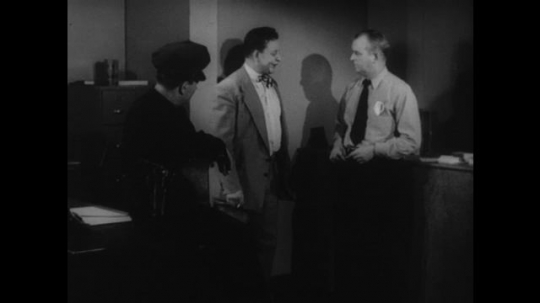 1950s: Two policemen question drunk man. Policeman in hat leaves the room. Second policeman gestures for drunk man to walk in a straight line.