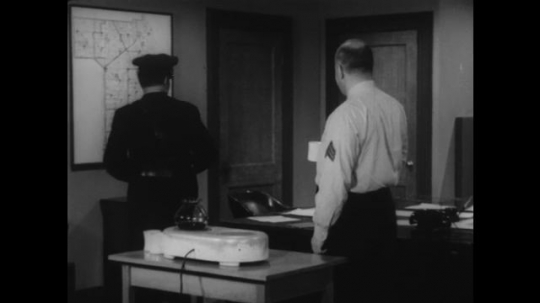 1950s: Sergeant and police officer walk towards the door. Sergeant and police officer stand by desks. A third policeman joins them with a file.