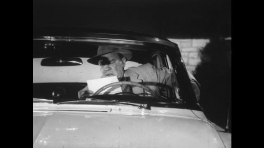 1950s: Man in suit and hat starts car and drives off. Driver talks into microphone. Driver is so distracted he almost hits pedestrian.