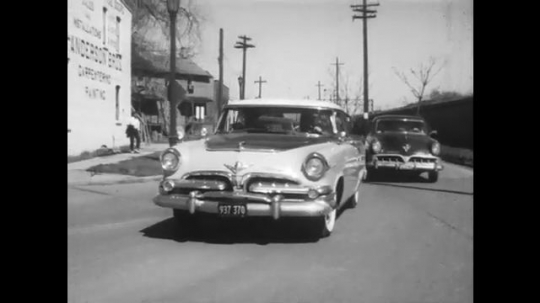 1950s: Car turns corner. Woman drives car with male passenger. Woman talking merrily, man reading papers. Man gestures to right. Woman brings car to a sudden stop.