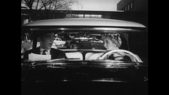 1950s: Woman driver and male passenger talk  in front seat of car. Car accelerates from stop. Car pulls over to curb and on to grass.