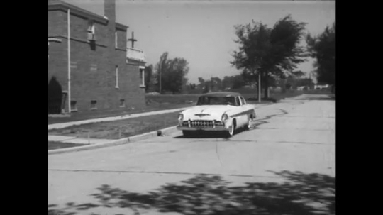 1950s: Car speeds around corner and almost hits elderly lady. Man drives car while dictating into microphone. Man laughs and drivers erratically.