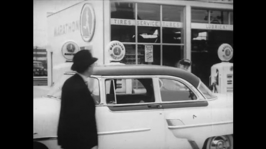 1950s: Car parked at Marathon gas station. Attendant tries to help driver but man is in hurry. Man drives away quickly.