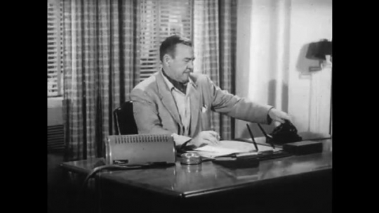 1950s: Man behind desk hangs up phone. Man speaks into office intercom and smokes a cigarette. Man yells and looks annoyed.